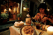 A woman sitting at a table having dinner, Trattoria al Trebbio, Florence, Tuscany, Italy, Europe