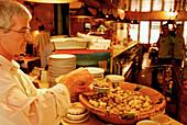 Owner Juan Hurtado placing olives on a plate, restaurant Pa amb Oli, Ciutadella, Minorca, Balearic Islands, Spain