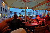 People enjoying a midnight coffee, Raekoja Plats, town hall square in the late evening in summer, Tallinn, Estonia