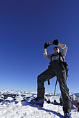 Backcountry skier taking summit shot with digital camera, Brechhorn, Kitzbuehel range, Tyrol, Austria