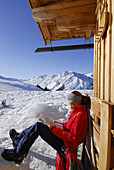 Female backcountry skier resting in front of alpine lodge while reading a map, Hirzer, Tux Alps, Tyrol, Austria