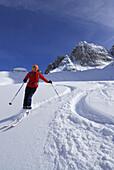 Woman downhill skiing through powder snow, Cadini range, Dolomites, South Tyrol, Alto Adige, Italy