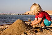 Little child, girl, 3, playing with sand on the beach of the Lamaya Resort, Coraya, Marsa Alam, Red Sea, Egypt