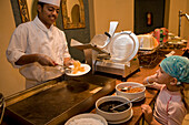 Cook preparing a pancake for a child, a girl, 5 at the buffet of Lamaya Resort, Coraya, Marsa Alam, Egypt