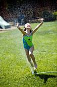 Young girl leaps through yard sprinkler