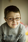Smiling boy with eye glasses.