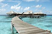 Board walk guiding to bungalows. Maldives Island, Indian Ocean.