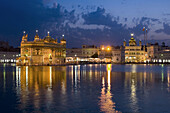 Sikh Golden Temple of Amritsar glowing at dusk, Punjab, India