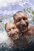 Couple ages 26 and 39 playing at poolside waterfall on a wonderful tropical holiday Beqa Lagoon Resort, Beqa Island, Fiji