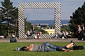 Framework by the artist group Haus-Rucke-Co for the documenta VI. This frame marks the border from Friedrichsplatz to the Karlsaue, female visitor sleeps on the lawn, Kassel, Hesse, Germany