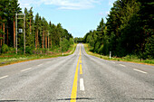 Empty country road between coniferous forests, Saimaa Lake District, Finland, Europe
