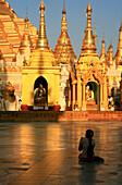 Praying buddhistic woman at the Shwedagon Pagoda in the evening, Rangoon, Myanmar, Burma, Asia