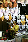 A vendor of lingerie reading newspaper, market, Rangoon, Myanmar, Burma, Asia