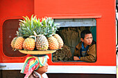 A woman selling fruit, a boy looking out of the window of a train, Hispaw, Shan State, Myanmar, Burma, Asia