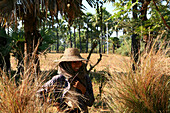 Laughing woman wearing a hat between palm trees, Myanmar, Burma, Asia