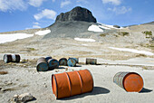 Fuel drums abandoned by miners and left to rust and leak into the wilderness watershed of Salal Creek, The Elephant, or sometimes called The Black Molar 2314 m 7592 ft is in the distance Coast Mountains British Columbia