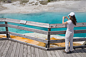 Woman taking photo of the Black Pool, Yellowstone National Park, Wyoming, USA