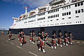 Pipe Band playing on the quay at Greenock, near Glasgow, on the Firth of Clyde, Scotland when the cruise liner Queen Elizabeth 2 berthed on 5th October 2008 while on its final voyage before being decommissioned in Dubai