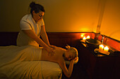 A woman receiving a massage by candlelight, Temple Mountain Spa, Post Hotel & Spa, Lake Louise, Alberta, Canada