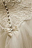 Adult, Adults, b&w, back view, black-and-white, Bow, Bows, bride, brides, Button, Buttons, Close up, Close-up, Closeup, Contemporary, detail, details, Dress, Dressed up, Dresses, Elegance, Elegant, Female, human, indoor, indoors, interior, Knot, Knots, ma