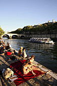France. Paris. People relax in later afternoon sun light during Paris Plage along the bank of River Seine.