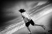 Joven corriendo en la playa. Costa Dorada en invierno. Tarragona (Spain)