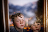 Two boys looking out a window, Brixen, Tyrol, Austria