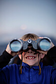 Boy (7 years) looking through binoculars, Brixen, Tyrol, Austria