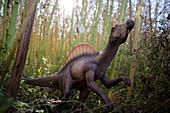 Toy spinosaurus amidst bamboo stalks