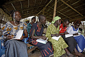 SOUTH SUDAN  Loka Womens Association  Concentrated expressions of women at an adult literacy class which is held in a simple rustic classroom at the Centre
