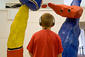 Boy listening to audio guide studying Miro sculpture. Miro Foundation, Barcelona, Spain