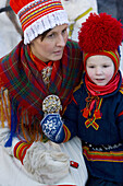 Sami (Lapp) boy with mother at Winter Fair. Jokkmokk, Northern Sweden