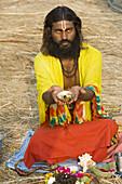 Sadhu doing puja (Hindu act of devotion) at Kumbh Mela festival. Allahabad, Uttar Pradesh, India