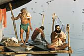 Man doing puja (Hindu devotional worship) by river Ganges at Kumba Mela festival