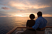 Couple standing at the railing of MV Columbus looking at sunset, South Pacific, Oceania