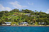 Houses at the coastline in the sunlight, Raiatea, Society Islands, French Polynesia, South Pacific, Oceania