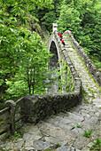 Two persons looking down from a stone arch bridge Ponte Romano over river Melezza, Intragna, Centovalli, lake Maggiore, Lago Maggiore, Ticino, Switzerland
