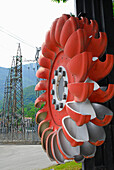Turbine wheel with electricity pylons in the background, Pelton turbine, water power plant near Chiavenna, Ciavenna, Lombardy, Italy