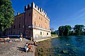 Menschen sitzen am Seeufer vor der Skaligerburg, Lazise, Gardasee, Venetien, Italien, Europa