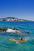 Girl on air matress off the beach of Primosten, Croatian Adriatic Sea, Dalmatia, Croatia, Europe