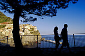 Couple walking hand in hand at Via dell´Amore hiking track, Manarola in the background, Cinque Terre, Liguria, Italian Riviera, Italy, Europe