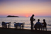 People on the seaside promenade at sunset, Island of Lesbos, Greece, Europe