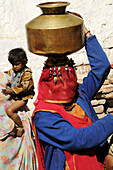 A big smile under the veil: a Rajasthani woman comes back home with fresh water pumped in the local well