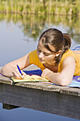 Young girl writing her diary at a lake