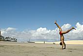Capoeira player training  in the beach, Jericoacora, Brazil.