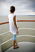 Adult, Adults, Back view, Boat, Boats, Brazil, Calm, Calmness, Color, Colour, Contemporary, Daytime, Deck, Decks, Exterior, Female, Fordlandia, Full-body, Full-length, Holiday, Holidays, Horizon, Horizons, Human, Leisure, Navigation, One, One person, Outd