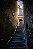 Alley, Alleys, Back view, Cities, City, Color, Colour, Dark, Daytime, Europe, Exterior, Human, Narrow, One, One person, Outdoor, Outdoors, Outside, People, Person, Persons, Rear view, Rear views, Single person, Stairs, Steps, Stockholm, Street, Streets, S