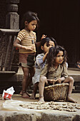 Young girls selling ginger in a street of the former royal city of Bhaktapur, valley of Kathmandu, Nepal