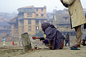 Couple making an offering at a stone marking the place of a former temple, Bhaktapur, valley of Kathmandu, Nepal
