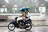 Young girls in motorbike under a heavy monsoon rain, Louang phra Bang, Laos